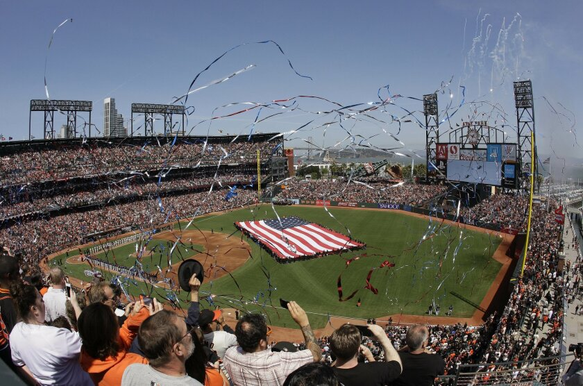 Fans cheer as confetti falls after the national anthem before the San Francisco Giants home opener baseball game against the Colorado Rockies in San Francisco, Monday, April 13, 2015. (AP Photo/Eric Risberg)