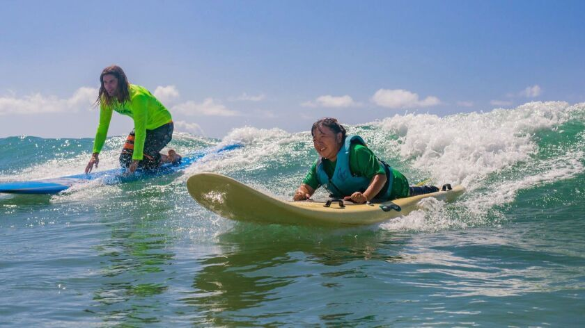 An AccessSurf volunteer and Atsuko Kuwana ride a wave at White Plains Beach on Oahu.