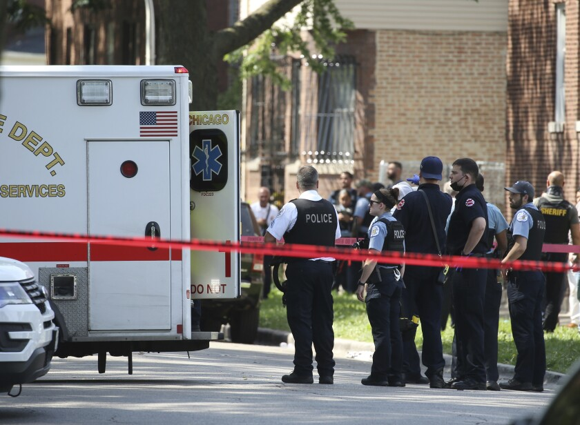 Chicago police and emergency medical personnel work at the scene of a police-involved shooting in Chicago, Friday, July 9, 2021. Law enforcement officers in Chicago shot and wounded a 33-year-old man who pointed a gun at them as they tried to arrest him Friday, authorities said. (Antonio Perez/Chicago Tribune via AP)
