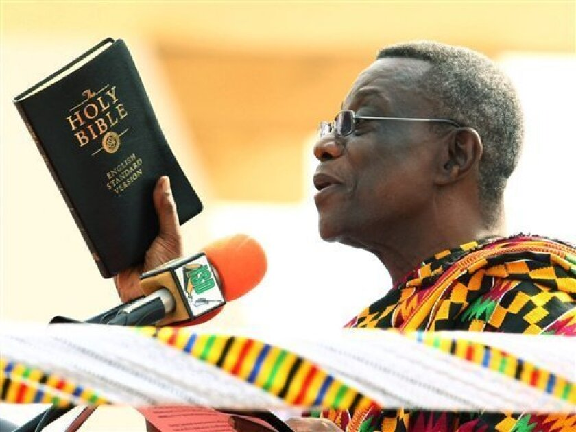 President-elect John Atta Mills holds a bible as he is sworn in as the country's new president during a ceremony in Accra, Ghana Wednesday, Jan. 7, 2009.  The election of Mills, in the closest vote in Ghana's history, makes the West African nation one of the few African countries to successfully tr