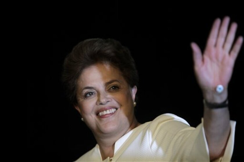 Brazil's Workers party presidential candidate Dilma Rousseff waves as she arrives for a press conference in Brasilia, Brazil, Sunday Oct. 3, 2010. Rousseff has been forced into a second-round runoff with Jose Serra, of the Brazilian Social Democratic party, PSDB, after failing to obtain fifty percent plus one of the total votes. The runoff is set for Oct. 31. (AP Photo/Natacha Pisarenko)
