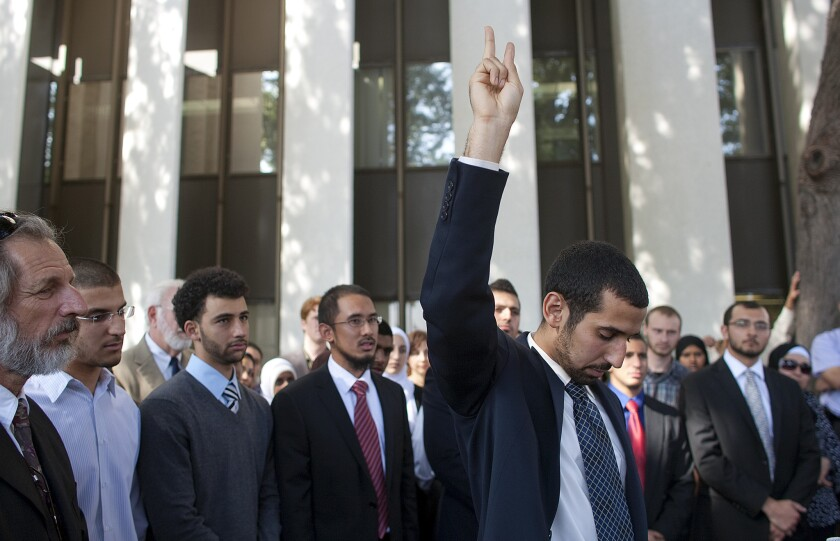 With his co-defendants standing behind, Muslim student Mohamed Mohy-Eldeen Abdelgany holds up a peace sign while speaking after he and the others were found guilty of disrupting a speech by the Israeli ambassador at UC Irvine.