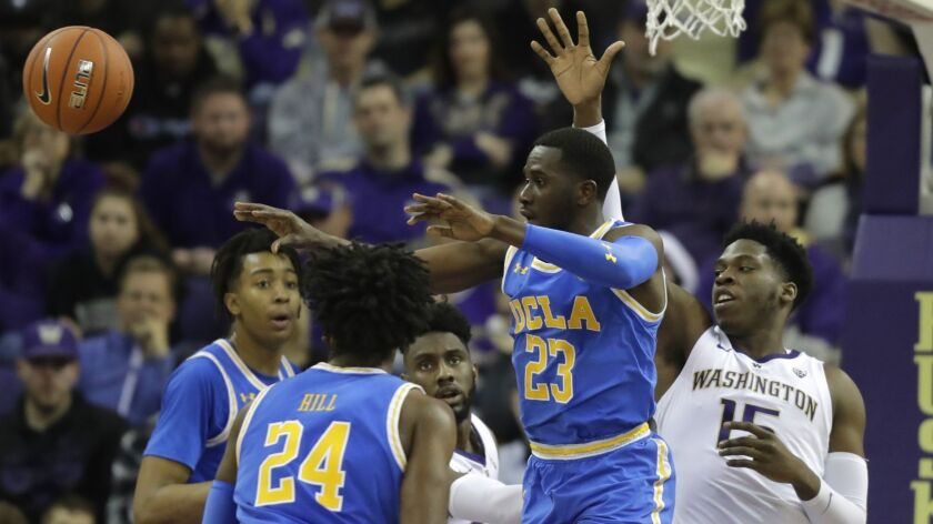UCLA guard Prince Ali (23) passes under pressure from Washington forward Noah Dickerson, right, duri