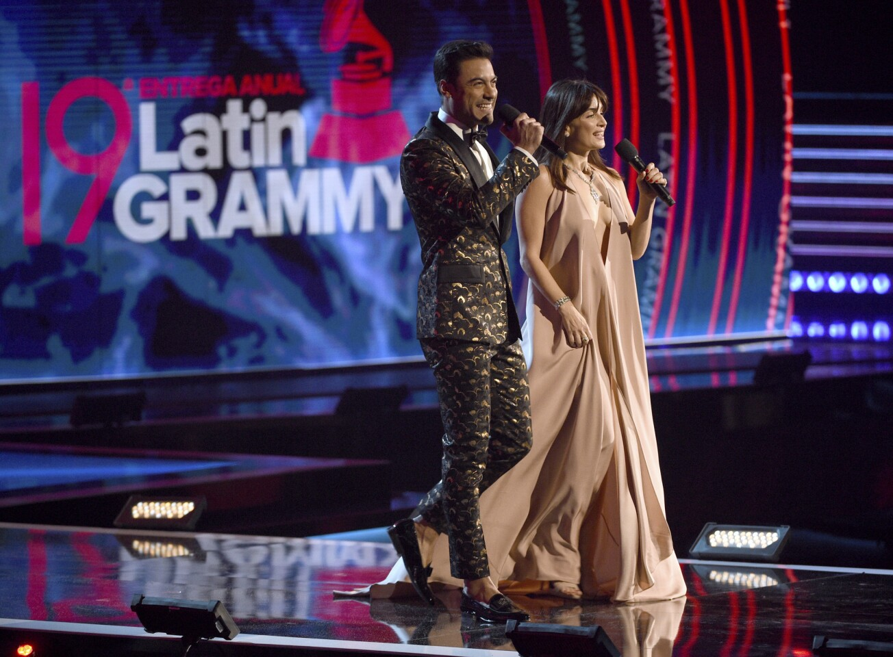 Hosts Carlos Rivera, left, and Ana De La Reguera speak at the Latin Grammy Awards at the MGM Grand Garden Arena in Las Vegas.