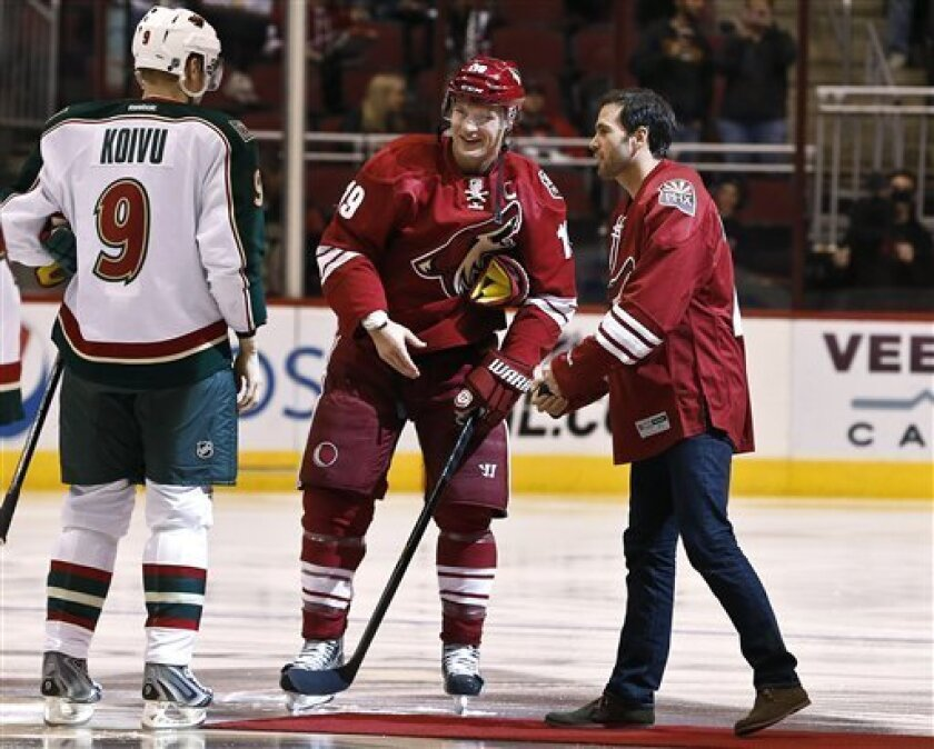NASCAR driver Jimmie Johnson, right, talks to Phoenix Coyotes' Shane Doan (19) and Minnesota Wild's Mikko Koivu (9), of Finland, prior to Johnson dropping the ceremonial first puck before an NHL hockey game, Thursday, Feb. 28, 2013, in Glendale, Ariz. (AP Photo/Ross D. Franklin)