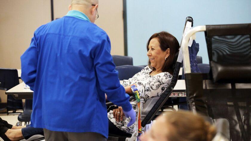 Diana Abasta the President of the Burbank Teacher Association, donates blood during the Evie Swiercz
