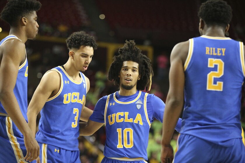 Tyger Campbell reaches out to pull in several other UCLA basketball players on court.