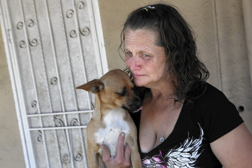 Kathleen Anderson holds her dog Mugsy; her husband, Johnny Ray Anderson, was fatally shot by a sheriff's deputy July 5 and the Hawaiian Gardens City Council has asked for an FBI investigation of the shooting.