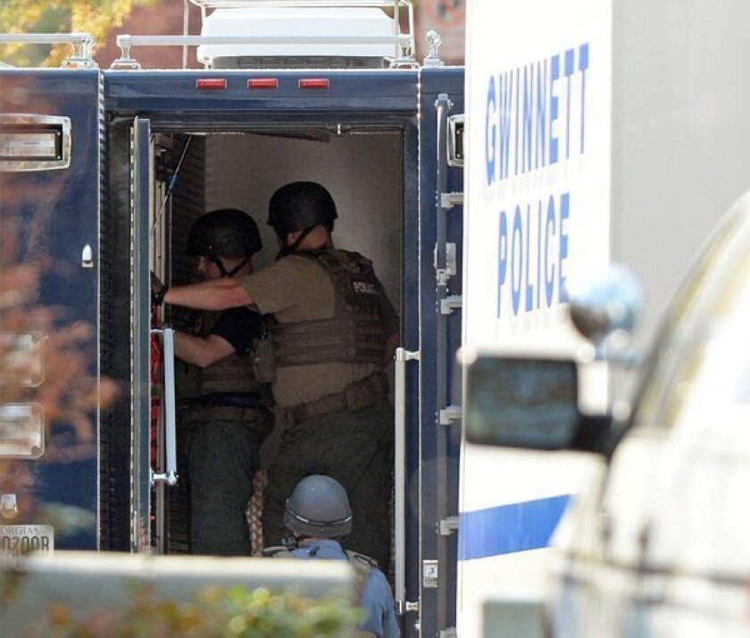 The Gwinnett County police work at the home in Suwanee, Ga., where five firefighters had been taken hostage.