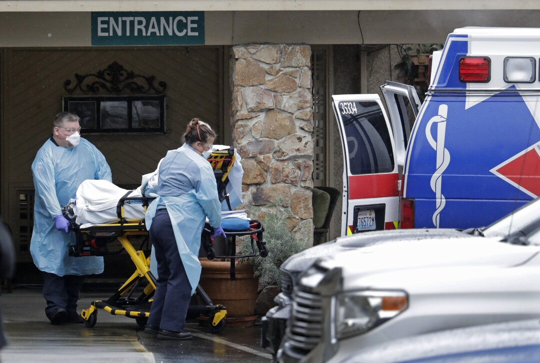 Ambulance workers transfer a man on a stretcher from the Life Care Center in Kirkland, Washington, to an ambulance.