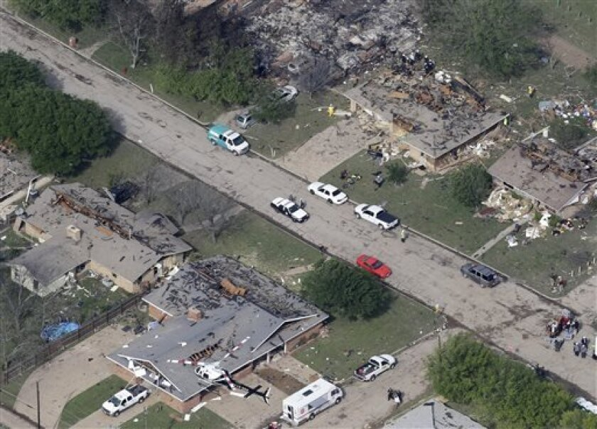 In this Thursday, April 18, 2013 photo, emergency personnel investigate the scene of several homes destroyed by an explosion at the West Fertilzer Co. in West, Texas. Rescuers searched the smoking remnants for survivors of Wednesday night's thunderous fertilizer plant explosion, gingerly checking smashed houses and apartments for anyone still trapped in debris while the community awaited word on the number of dead. Initial reports put the fatalities as high as 15, but later in the day, authoriti