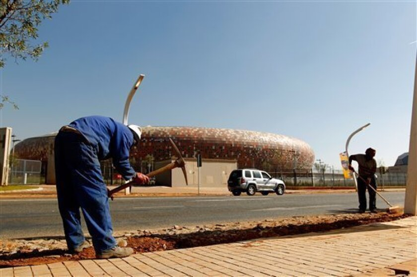 Preparations continue as the Soccer City stadium, background, gets ready for the Soccer World Cup in Johannesburg, South Africa, Thursday, June 3, 2010. The tournament is to be kicked off on June 11. (AP Photo/Hassan Ammar)