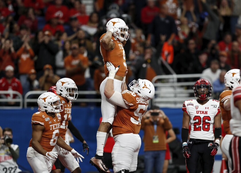 Zach Shackelford lifts Collin Johnson after scoring a touchdown against Utah during Texas' 38-10 victory in the Alamo Bowl.
