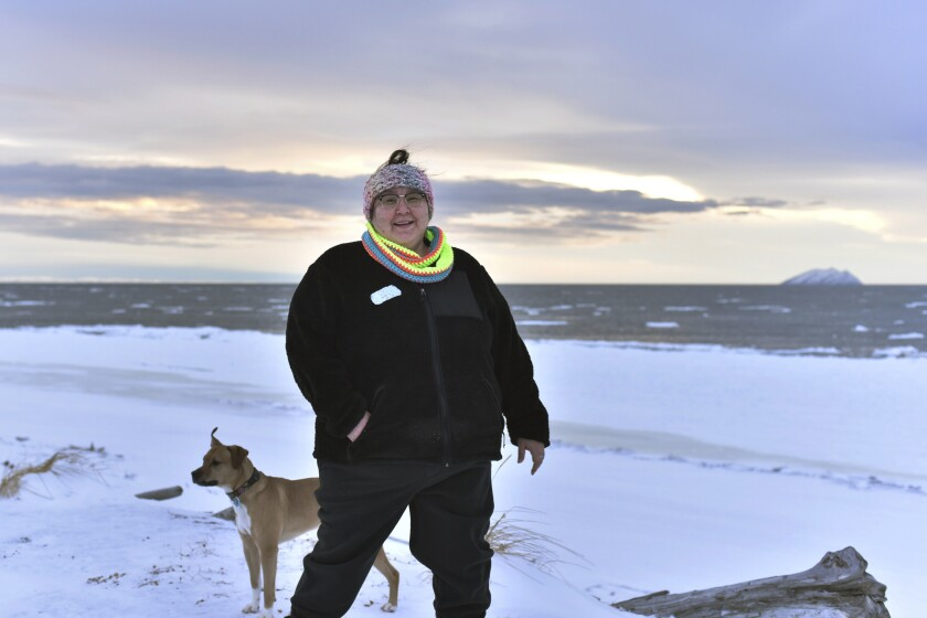 """FILE - In this Jan. 14, 2019 photo, Clarice """"Bun"""" Hardy, who is of Inupiaq heritage, stands on the beach with her dog, Marley, in the Native Village of Shaktoolik, Alaska. On Tuesday, Sept. 24, 2019, the American Civil Liberties Union's Alaska branch demanded that the city pay $500,000 to compensate the former 911 dispatcher who says her colleagues at the police department failed to investigate her report that a man had raped her in her home. The ACLU accused the Nome Police Department of """"a systemic and disastrous failure"""" to keep Alaska Native women safe from sexual assault. (AP Photo/Victoria Mckenzie)"""