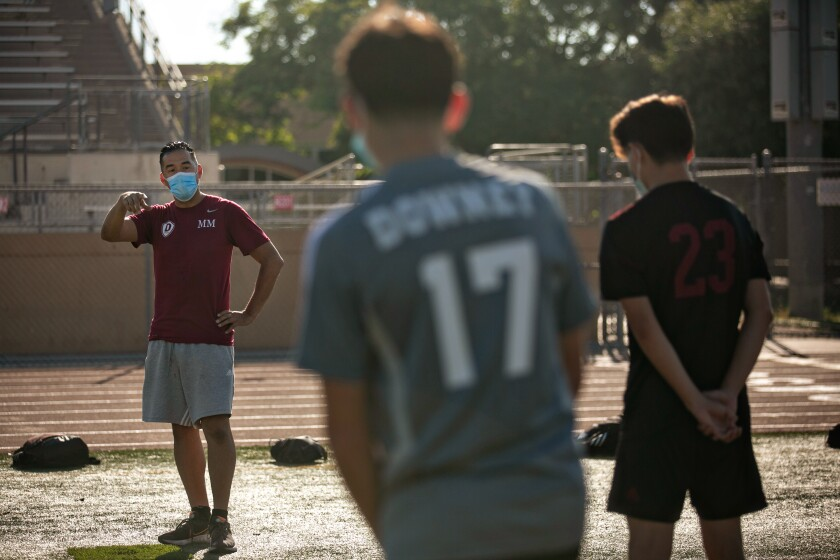Downey High soccer coach Marvin Mires speaks to the team before practice on Oct. 30, 2020.