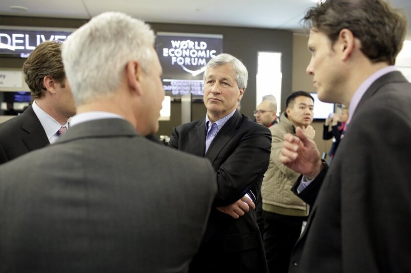 They may think they're doing God's work, but the Pope begs to differ: JPMorgan chief Jamie Dimon, center, during a break at the Davos World Economic Forum.