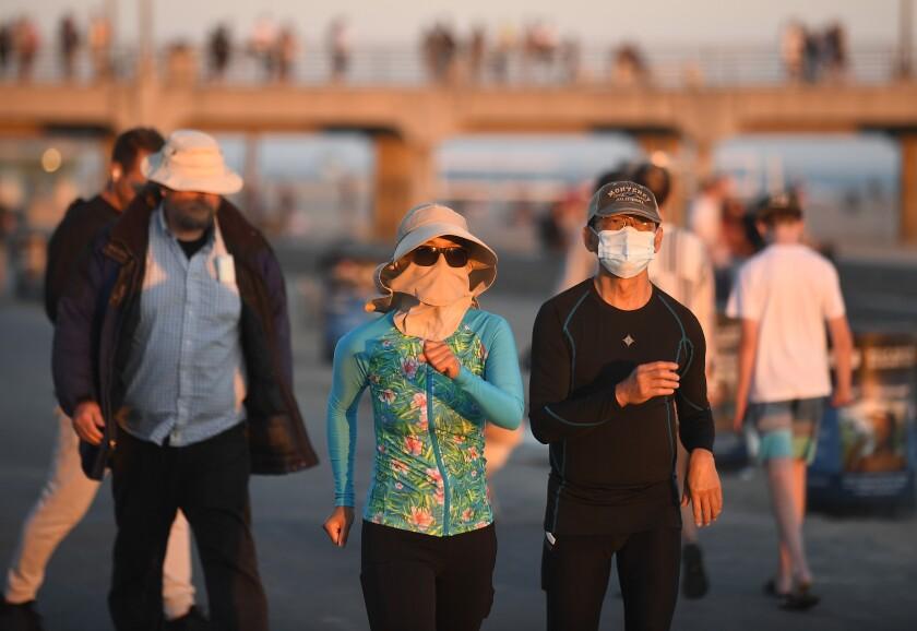 Pedestrians walk in Huntington Beach