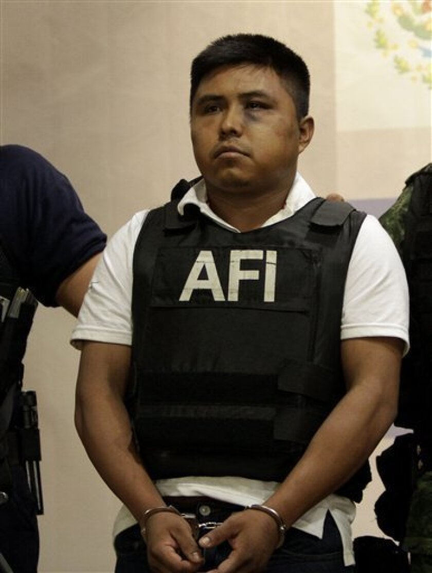 "Abraham Barrios Caporal, alias ""Erasmo,"" is shown to the media during a news conference in Mexico City, Thursday June 30, 2011. Barrios, who was detained by Army soldiers on Tuesday, is allegedly a member of Los Zetas drug cartel and was presumably involved in the kidnapping and killing of people f"