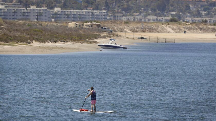 A paddleboarder makes his way through Mission Bay in June. A report on potential impacts of climate change warns that electrical substations in the Mission Bay and San Diego Bay areas could be vulnerable to rising sea levels in the coming decades.