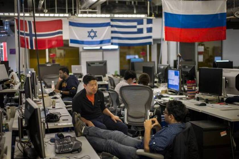 Sitting below flags from around the world, growth team member George Lee, left, speaks with Vishu Gupta at Facebook's Menlo Park headquarters. The company is pushing its global reach.