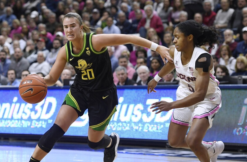 Oregon's Sabrina Ionescu, left, dribbles around Connecticut's Crystal Dangerfield in the second half on Feb. 3 in Storrs, Conn.