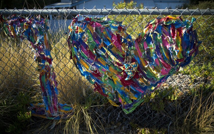 """Carmen Costello's """"One Love"""" was created out of tablecloth strips from a friend's anniversary party. It is woven into a fence near her North Park home."""