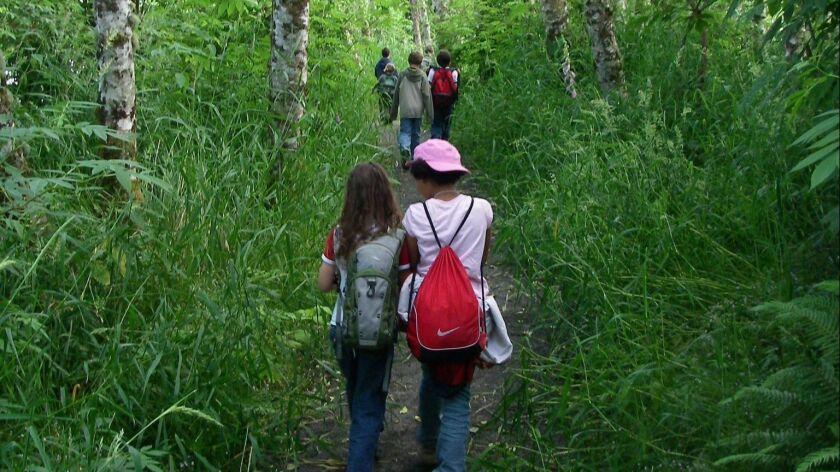 Children hike on a forested trail in Lewis and Clark National Historical Park in Oregon.