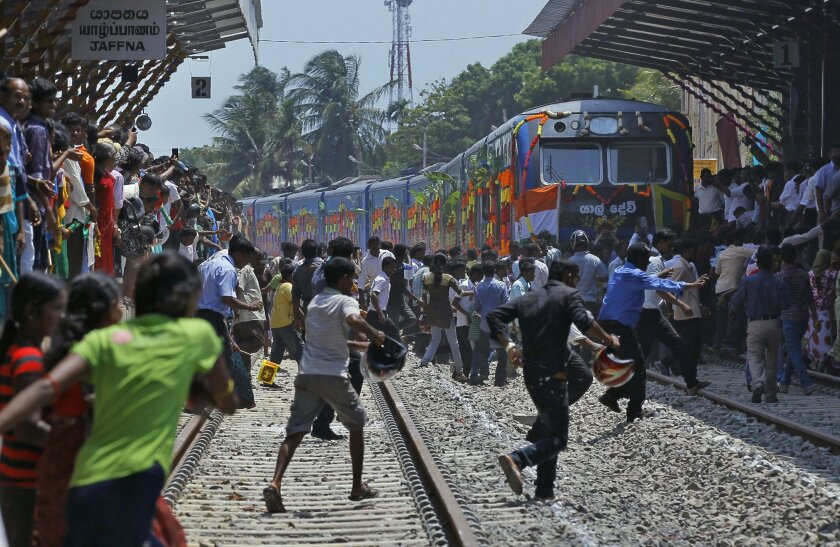 """Sri Lankan ethnic Tamils rush towards the train """"Queen of Jaffna,"""" after it arrived at Jaffna in Sri Lanka, Monday, Oct. 13, 2014. The once-popular train linking the ethnic Tamil's northern heartland to the rest of Sri Lanka arrived in Jaffna, 24 years after its suspension due to the country's civil war. (AP Photo/Eranga Jayawardena)"""