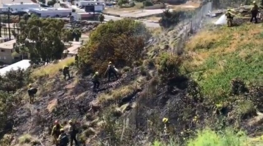 Firefighters work to fully extinguish a vegetation fire that burned near homes Thursday afternoon in the Chollas Creek neighborhood of San Diego.