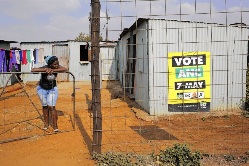 A woman rests outside her home near an African National Congress party campaign poster in Bekkersdal, near Johannesburg, South Africa. The party is expected to hang on to power in Wednesday's national elections.