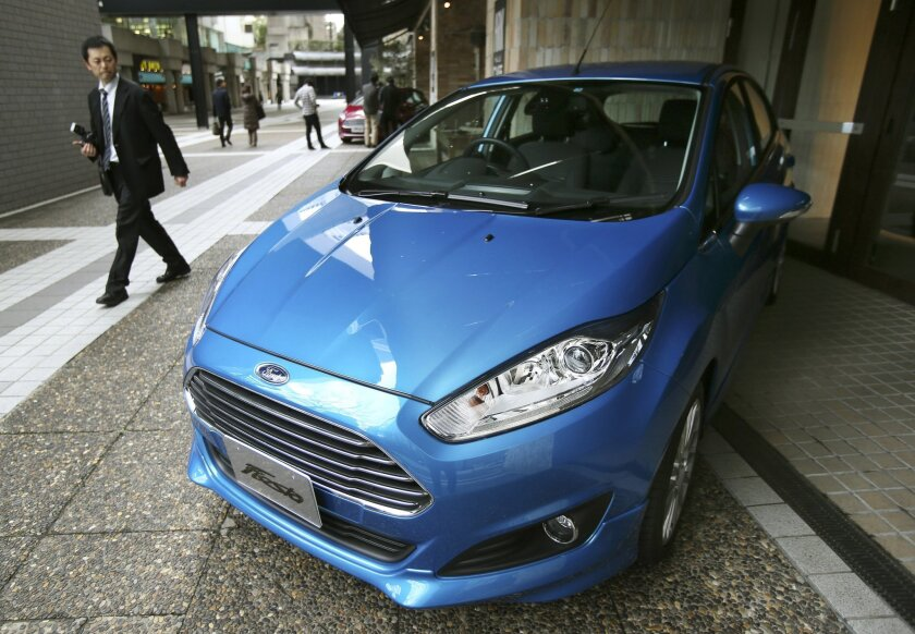 """FILE - In this Thursday, Jan. 9, 2014, file photo, a man looks at a Ford Fiesta compact car in Tokyo. Ford Motor Co. said Monday, Jan. 25, 2016, that it's pulling out of Japan and Indonesia before the end of the year because there is no path to grow sales or make sustained profits. The automaker says """"market dynamics"""" prevent it from competing effectively in both of the countries, so it will cease operations and concentrate resources elsewhere. (AP Photo/Koji Sasahara, File)"""