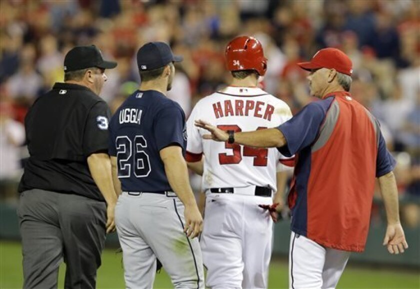 Washington Nationals hitting coach Rick Schu, right, walks with Bryce Harper (34) as Atlanta Braves second baseman Dan Uggla (26) and umpire Sam Holbrook (34), walk along side, after Harper was hit by a pitch during the fifth inning of a baseball game at Nationals Park Tuesday, Aug. 6, 2013, in Washington. (AP Photo/Alex Brandon)