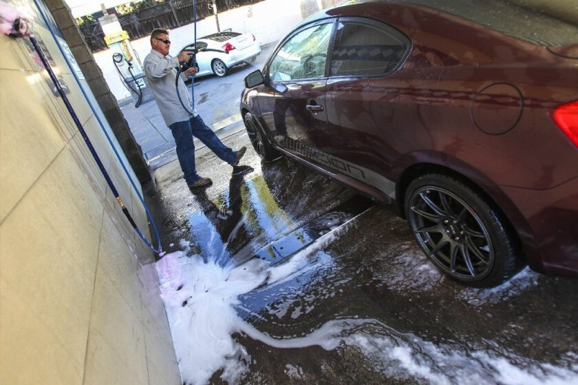Washing your vehicle at a commercial facility, such as this one on University Avenue in San Diego city, instead of in your driveway or on the street can help reduce the level of pollutants entering storm drains and eventually the ocean. / photo by Hayne Palmour IV * U-T