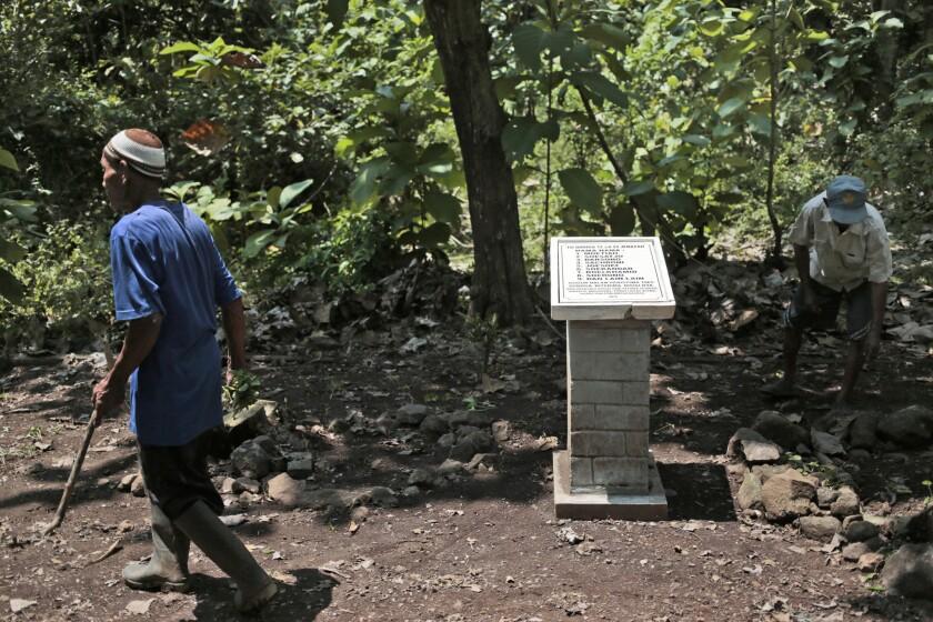 Asrori (izq) y Sukar, dos testigos de la matanza, fotografiados junto a una placa con los nombres de ocho personas supuestamente asesinadas en este aislado paraje cerca de Plumbon, Indonesia, el 3 de septiembre del 2016. La placa, colocada el año pasado, es el primer monumento conmemoratorio de la matanza de hasta medio millón de personas durante una campaña anticomunista a mediados de la década de 1960. La historia oficial borró de la memoria colectiva ese período sangriento, pero ahora la gente está empezando a hablar de nuevo. (AP Photo/Dita Alangkara)