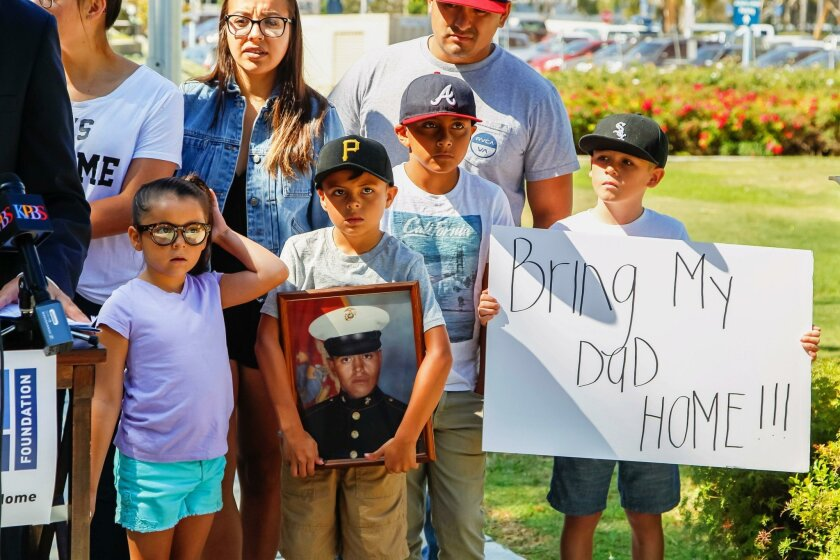 Family members of deported veteran Enrique Salas (Marine in framed photo) attend a press conference at the Veterans Museum in Balboa Park on Wednesday in San Diego, California.