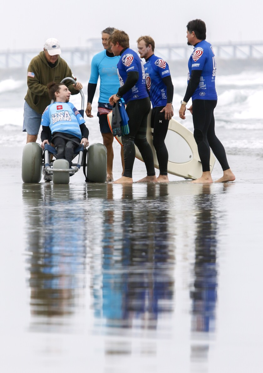 Surfer Dylan Hronec talks with his team before competing in his prone assist contest at the USA Surfing Adaptive Surfing Championship at Oceanside Harbor North Jetty.