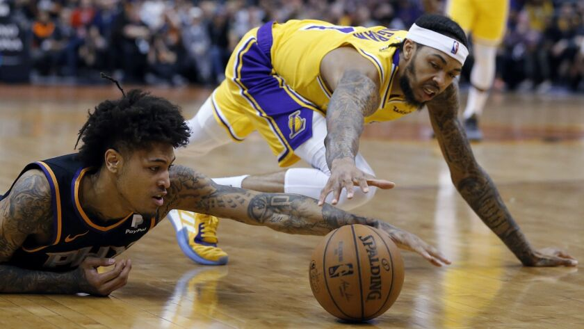 Phoenix Suns forward Kelly Oubre Jr., left, dives for a loose ball in front of Los Angeles Lakers fo