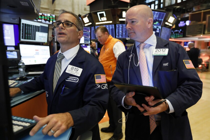 FILE - In this Sept. 13, 2019, file photo specialist Anthony Rinaldi, left, and trader Patrick Casey work on the floor of the New York Stock Exchange. The U.S. stock market opens at 9:30 a.m. EDT on Friday, Oct. 4. (AP Photo/Richard Drew, File)