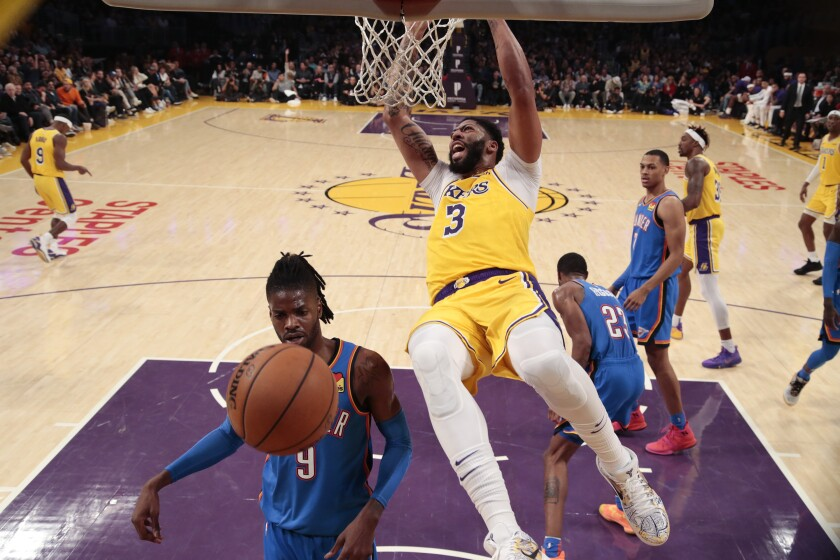 Lakers forward Anthony Davis slams over Oklahoma City Thunder center Nerlens Noel during second-half action at Staples Center on Nov. 19.
