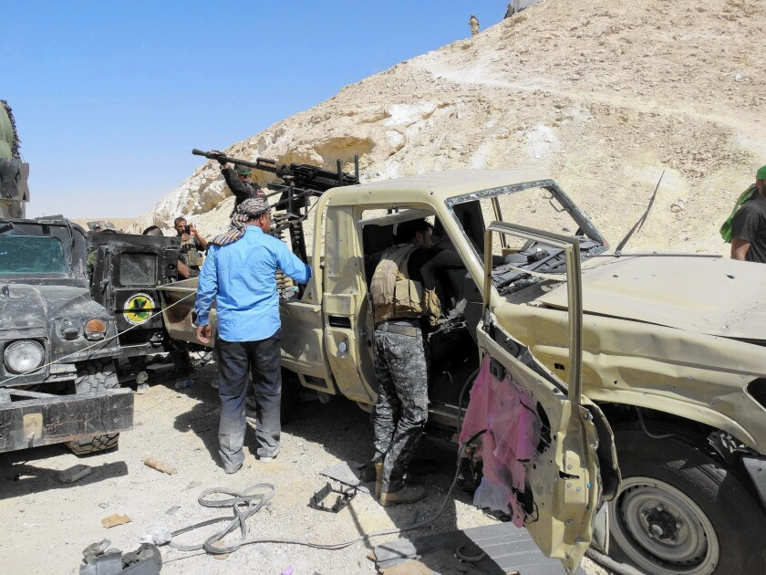 Iraqi security forces and Sunni tribesmen inspect damaged vehicles after an attack this week on a military post in Anbar province, in western Iraq.