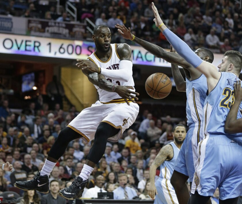 From left to right, Cleveland Cavaliers' LeBron James passes around Denver Nuggets' JaKarr Sampson and Jusuf Nurkic, from Bosnia, in the first half of an NBA basketball game Monday, March 21, 2016, in Cleveland. (AP Photo/Tony Dejak)