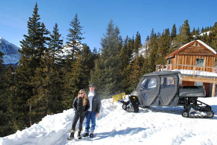 In this Jan. 24, 2014 photo, Andy and Ceil Barrie stand for a photo next to their mining cabin near Breckenridge, Colo. Summit County wants to condemn 10 acres of land that belongs to the Barrie's through the controversial power of eminent domain. (AP Photo/Nicholas Riccardi)