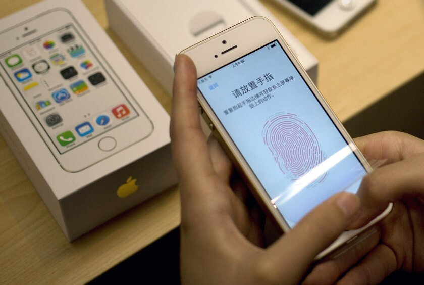 FILE - In this Sept. 20, 2013 file photo, a customer configures the fingerprint scanner technology built into the Apple iPhone 5S at an Apple store in Wangfujing shopping district in Beijing. Beyond unlocking the phone, the fingerprint can be used to authenticate the purchase of apps and content within apps. This fall, Apple will begin letting outside developers use the fingerprint ID as part of their apps. (AP Photo/Andy Wong, File)