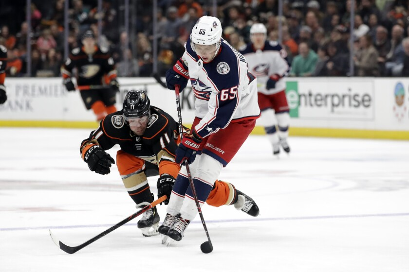Columbus Blue Jackets' Markus Nutivaara, right, controls the puck next to Ducks' Daniel Sprong during the second period on Tuesday at the Honda Center.