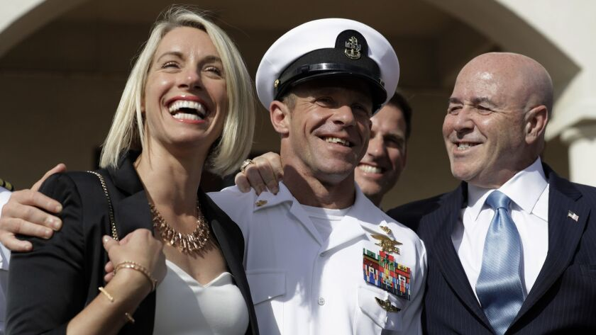 Navy Special Operations Chief Edward Gallagher, center, walks with his wife, Andrea Gallagher, left,