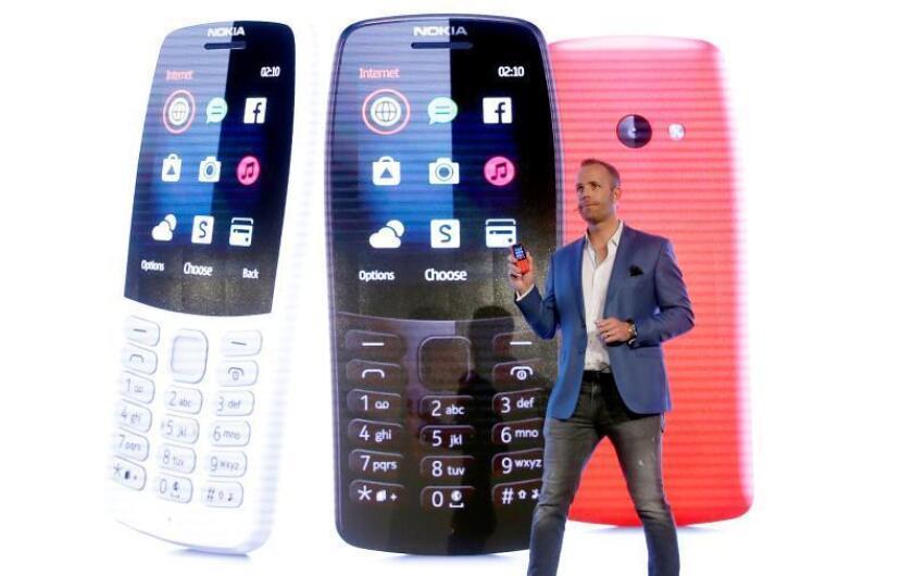 El director de producto de HMD, Juho Sarvikas, muestra un Nokia 210 durante el acto de presentación de los nuevos modelos de móviles Nokia este domingo en un evento previo al comienzo del Congreso Mundial de Móviles que empezará mañana en Barcelona. EFE