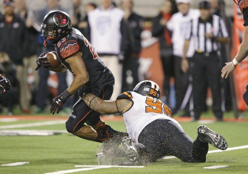 Utah running back Devontae Booker (23) runs through the tackle of Oregon State defensive tackle Kyle Peko (99) in the second half during an NCAA college football game Saturday, Oct. 31, 2015, in Salt Lake City. Utah won 27-12. (AP Photo/Rick Bowmer)