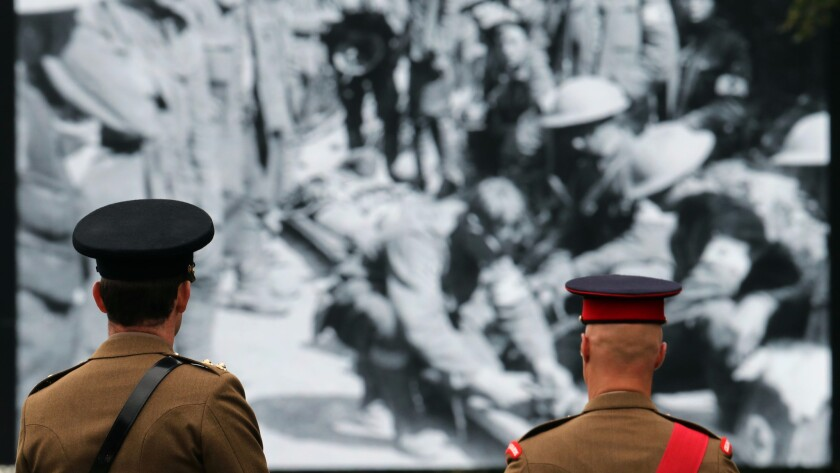 Servicemen watch footage of soldiers from the Battle of the Somme during ceremonies marking the centennial of the battle in Thiepval, France, on Friday.