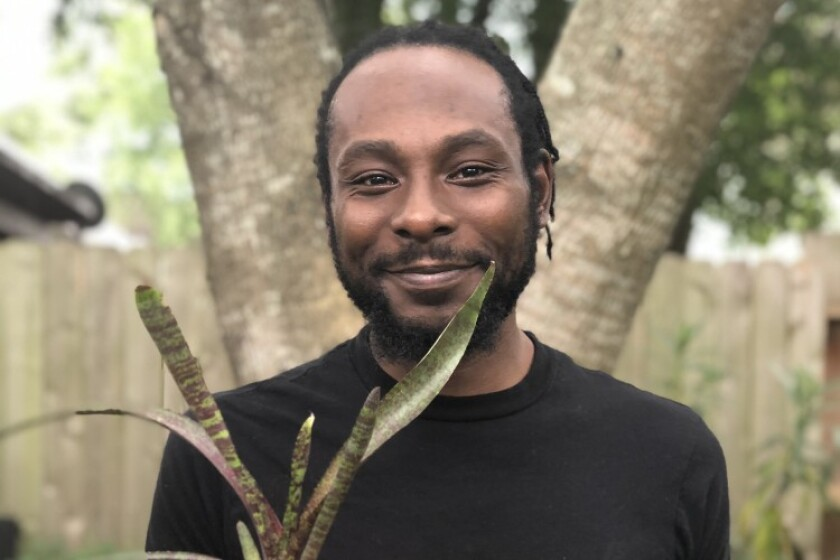 Marcus Bridgewater smiles, holding a potted plant.