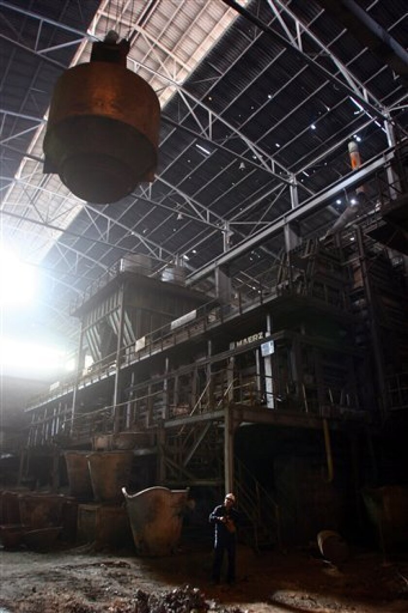 In this Feb. 16, 2007 file photo, smelters work at the newly nationalized Vinto tin smelter in the outskirts of Oruro, Bolivia. Swiss-based Glencore International AG's Bolivian subsidiary just announced it will layoff several hundred employees which is triggering protests by the out-of-work miners